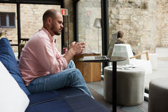 Male freelancer thoughtfully looking to the notebook screen while sitting at sofa in modern coffee shop interior. Pensive business man sitting front open laptop Stock Image