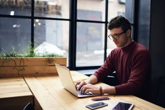 Male freelancer watching training webinar using free wireless connection to wifi in coworking space. Young concentrated male copywriter in eyewear typing text on Stock Photo