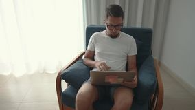 Alone adult man is working with laptop sitting in apartment in daytime. Male freelancer is working by internet with notebook in flat. He is sitting in chair in stock video