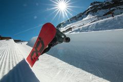 Snowboard Freestyle Snowboarding Half Pipe Jumping Air Sun. A male freestyle snowboarder rides down the half pipe, jumping into the air with the radiating Royalty Free Stock Image