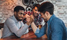 Male friends arm wrestling each other in bar. Male friends arm wrestling each other, drinking beer in bar stock photo