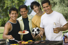 Male Friends Barbecuing Food At Park Royalty Free Stock Photography