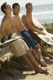 Male Friends On Beach. Happy ethnic male friends on beach with surfboards Stock Photography