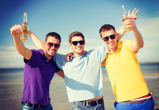 Male friends on the beach with bottles of drink. Summer, holidays, vacation and people concept - group of male friends having fun on the beach with bottles of Stock Photo