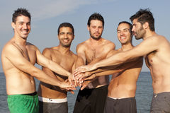 Male friends on the beach. Men putting their hands on each others hands Royalty Free Stock Photography