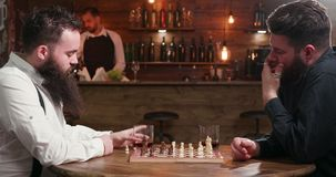 Male friends with beards met in a bar to play a chess game stock video