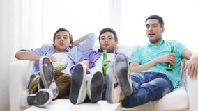 Male friends with beer watching tv at home Royalty Free Stock Photos