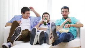 Male friends with beer watching tv at home Stock Photo