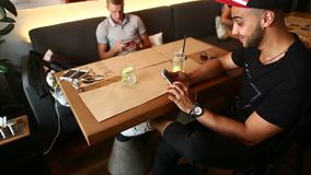 Male friends in cafe talk discuss with technology phone tablet stock video footage