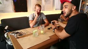 Male friends in cafe talk discuss with technology phone tablet stock footage