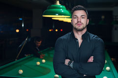 Male friends in club playing billiard game. Young handsome man wearing black casual cloth posing on the background of green snooker table Royalty Free Stock Images