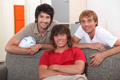 Male friends on a couch. Three male friends on a couch Stock Photo