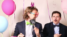 Male friends dancing with a sign in love in photo booth. Happy male friends dancing with a sign in love in photo booth stock video
