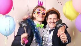 Male friends dancing with a sign in love in photo booth stock video