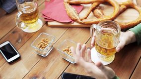 Male friends drinking beer at bar or pub. People, men, leisure, friendship and communication concept - two male friends drinking beer and clinking glasses with stock footage