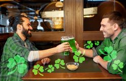 Male friends drinking green beer at bar or pub. Leisure, friendship, st patricks day and celebration concept - happy male friends drinking green beer and Stock Images