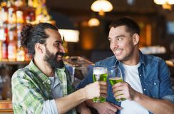 Male friends drinking green beer at bar or pub. Leisure, friendship, st patricks day and celebration concept - happy male friends drinking green beer and Stock Photos