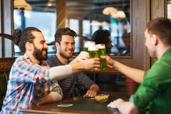 Male friends drinking green beer at bar or pub. Leisure, friendship, st patricks day and celebration concept - happy male friends drinking green beer and Royalty Free Stock Photo