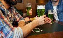Male friends drinking green beer at bar or pub. People, leisure and st patricks day concept - happy male friends drinking green beer at bar or pub Royalty Free Stock Photo