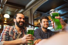Male friends drinking green beer at bar or pub. People, leisure and st patricks day concept - happy male friends drinking green beer at bar or pub Stock Images
