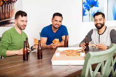 Male friends eating pizza at home Stock Images