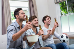 Male friends enjoying beer while watching soccer match on TV. Young male friends enjoying beer while watching soccer match on TV stock photography