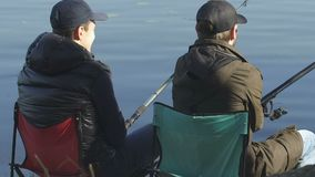Male friends fishing, sitting on folding chairs, recreational activity outdoor. Stock footage stock footage