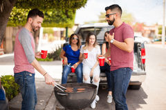 Male friends grilling hamburgers outdoors. Two handsome male friends grilling hamburgers for their friends while having barbecue on the street Stock Images