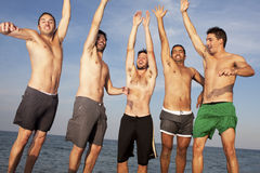 Male friends having fun on the beach Stock Image