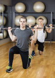 Male Friends Lifting Barbell In Gym Royalty Free Stock Images