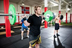 Male Friends Lifting Barbells In Fitness Center. Young male friends lifting barbells in fitness center Stock Photo