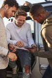Male friends planning road trip with tablet computer, vertical stock photography