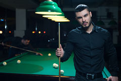 Male friends playing billiard game in club. Young caucasian or middle aestern man standing with cue, green snooker table with balls on background Royalty Free Stock Photography