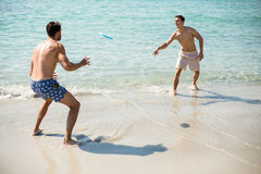 Male friends playing frisbee on shore at beach. Full length of shirtless male friends playing frisbee on shore at beach Stock Photography