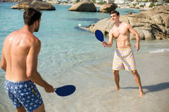 Male friends playing matkot on shore at beach. Shirtless male friends playing matkot on shore at beach Royalty Free Stock Image
