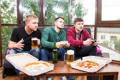 Male friends playing video games, drink beer and have fun at home Stock Photo