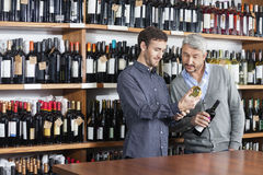 Male Friends Reading Label Of Wine Bottles In Shop Royalty Free Stock Photos