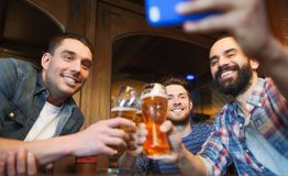 Male friends with smartphone drinking beer at bar Stock Photos