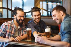 Male friends with smartphone drinking beer at bar Royalty Free Stock Photography