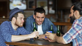 Male friends with smartphones drinking beer at bar stock video footage