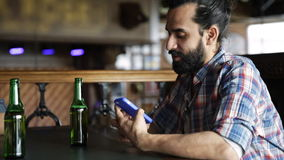 Male friends with smartphones drinking beer at bar stock video