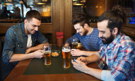 Male friends with smartphones drinking beer at bar Stock Image