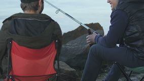 Male friends spending time together enjoying fishing and beer drinking, activity. Stock footage stock video