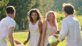 Male friends splashing buckets of water on beautiful ladies, friends having fun. Stock footage stock footage