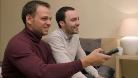 Male friends switch on and watch tv sitting on sofa at home. Close up. Professional shot in 4K resolution. 072. You can use it e.g. in your commercial video Royalty Free Stock Photo