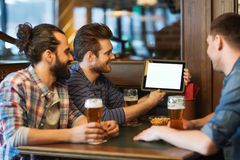 Male friends with tablet pc drinking beer at bar. People, men, leisure, friendship and technology concept - happy male friends with tablet pc computer drinking Royalty Free Stock Images