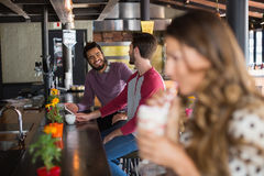 Male friends talking while sitting in restaurant Royalty Free Stock Image