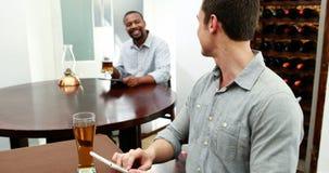 Male friends using digital tablet in restaurant 4k stock footage