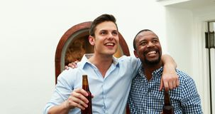Male friends watching football match while having beer 4k stock video footage