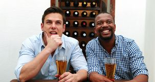 Male friends watching football match while having beer 4k stock footage